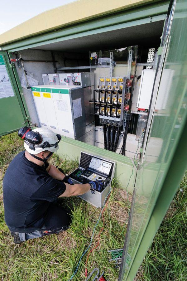 Außendienst-Mitarbeiter führt die DGUV V3 Prüfung für Windenergieanlagen durch